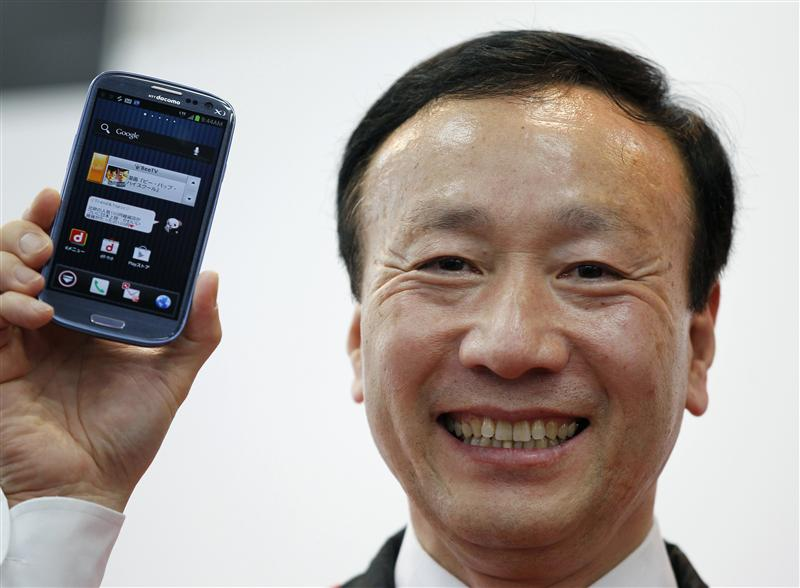 Kaoru Kato, president and CEO of NTT Docomo Inc, smiles while holding Samsung's Galaxy S III smartphone during a launch event at an electronics store in Tokyo